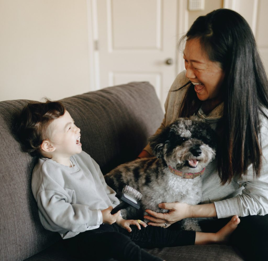 woman and child sitting on couch laughing while holding a small dog and dog brush