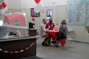 Three people sitting at a table wearing face masks talking in the adoption centre